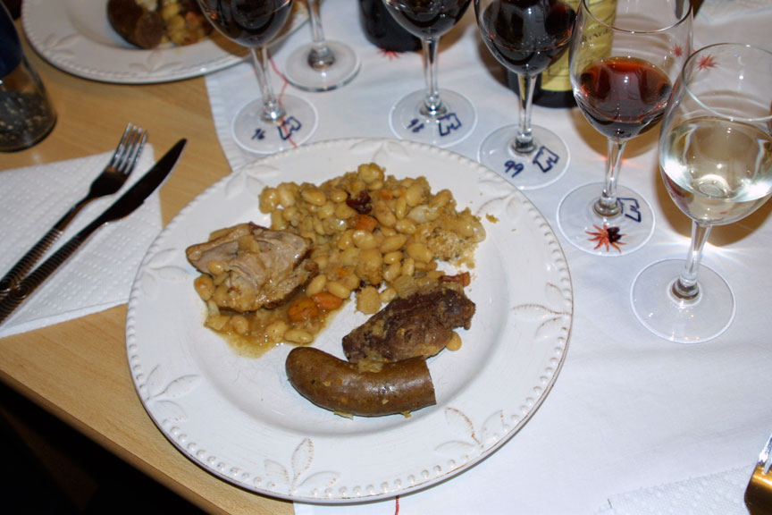 Cassoulet on a plate, surrounded by a halo of glassware